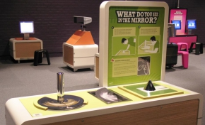 A cream and green coloured exhibit table and vertical information panel with the wording 'What do you see in the mirror?'. On the table are a chrome vertical short pole, a half circle and a black small inverted cone.