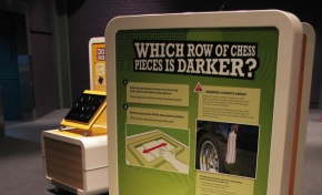 A cream and green exhibit table and information panel with the title 'Which row of chess pieces is darker?'.