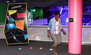A multi coloured sign with the words 'Optimusic' at the top, along side a carpeted area with a pink structural pole, and different coloured floor lights in a curved line. A teenage girl is walking on the lights.