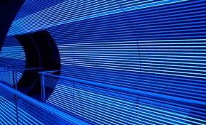 White and blue led lights line the inside of a large cylinder you can walk through. There is also hand railing in the photo.