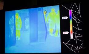 A monitor showing the room in a blue colour, with green, yellow and red shapes of people standing out.
