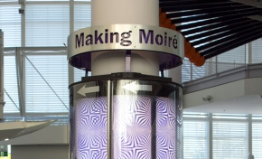 A blue and white pillar in a glass and white foyer, with a sign at the top saying 'Making Moire'.