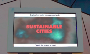 A computer monitor with the words Sustainable Cities, sitting on a timber display.