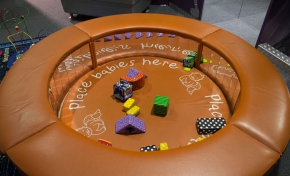 """A round padded tan coloured play area with mirrors in the inside wall and assortment of soft toys in the centre area. The words """"Place babies here"""" is written on the padded floor."""