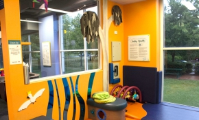 A brightly coloured room of yellow, blue and purple, with windows looking to outside garens, and soft play matts and baby toys on the ground.