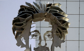 """A metal sculpture of Albert Einstein's head and shoulders sitting on a concrete pillar with the scientific equation """"E = mc squared"""" written on the pillar."""