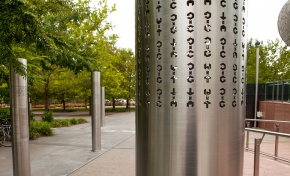 Four stainless steel vertical poles about 2 metres in height are spaced apart and embedded into a concrete and paved garden area. On each of the poles are laser cut out cryptographic symbols.
