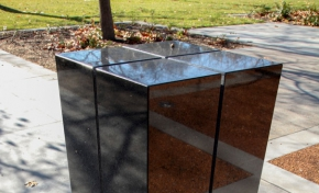 A rectangular black granite pilar about 1500 milimeters heigh, with for slits running from across the top to three quarters of the way down the sides. The pilar sits on concrete and is located in a garden environment.