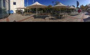 A panoramic photo of a courtyard with large umbrellas, tables and chairs and glass safetly railing. To the far left is a white wall and window with a large vertical blue dish, and to the right is a large red dish identical to the blue one. There are trees in the background.
