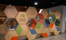 A hexagonial shaped sign in plywood, labeled Enterprising Australians, developed by Questacon