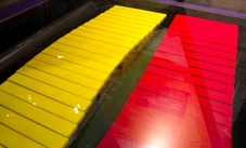 A yellow and red series of horizontal rods under a glass display.