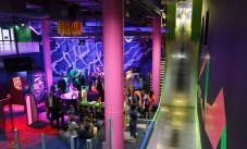 An overall view of the Excite @ Q exhibition, with a bright green and steel slide, pink support building poles, glass dividers and lots of people mingling.
