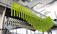 A row of vertical green pipes in a wave formation, sit under a overhead walkway. They both sit within a large foyer.