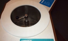 The coriolis exhibit, showing a white bench top with a circular hole cut out, and a stainless steel bowl with water components and a handle in the centre of the hole.