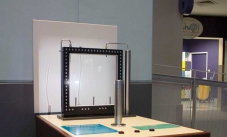 The convection current exhibit, consisting of a display table with a silver pole in in the centre, a black framed glass window, and then a white screen showing convection shadows.