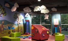 A brightly coloured play room with a billabong scene on one wall, cut out clouds hanging from the ceiling, and an array of play objects in the picture.
