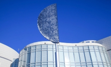 A large D shaped silver sculpture sitting on a pole with thousands of small metal round discs attached. Behind is a curved white building with many windows and a blue sky.