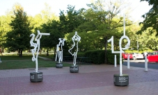 Four white steel outline scupltures of people on a paved area with gardens in the background.