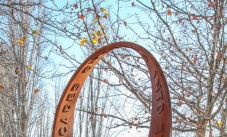 A rusted continuous steel loop sculpture with the raised words 'looping cascades'  and 'into sprial worlds' on the surface of the strip. The sculpture sits on a brown graveled garden area, with deciduous trees in the background.