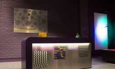 a stainless steel and black table with a curiosity corner sign hanging on the purple wall behind it