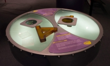 a round light table with purple and yellow information panels on the top, along with a triangle and two plastic polarised filters
