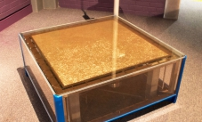 a low display case of blue steel and perspex, with a flat gold screen top of vibrating pins