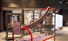 the pendulum snake exhit, made of a red steel frame with the closest end shorter than the back end, perspex sides, and pendulum balls suspended by string.
