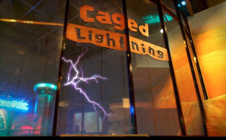 A large glass cage with the sign 'Caged Lightening' in orange at the top, and a lightening arc coming off a cylinder/dome structure inside