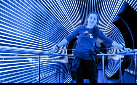 A girl standing in a blue and white lit tunnel and holding onto hand rails with each hand. She is leaning to one side.