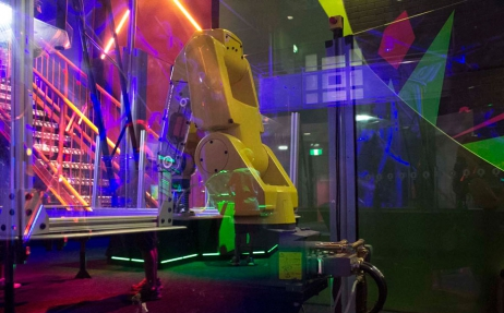 a yellow robot arm with a hocky puck attached at the end of it's arm sitting on a blue air hockey table