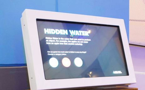 A monitor with Hidden Water exhibition information displayed.