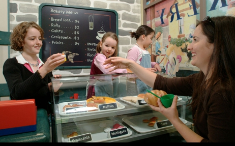 Three young girls playing in a toy bakery, and serving a woman.