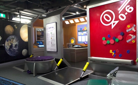 A large red magnetic sign holding colourful magnets in the shape of cogs and numbers, a wall painted with planets and the entrance way to a pretend space ship
