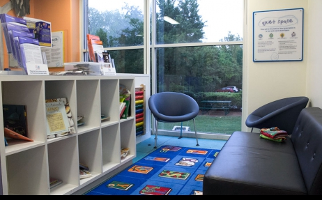 A light lit room with a bookshelf and books, a play rug, a leather couch, two seats and a window looking to the outside garden.