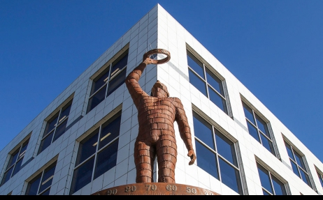 A rusted metal sculpture of a man holding a ring up to the sky with one outstretched arm. Behind him is the corner of a large white building with dark windows and a cloudless blue sky.