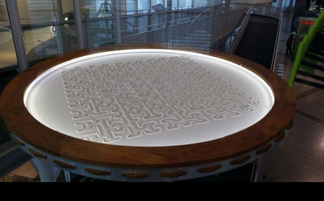 a flat circle of sand with geometric square patterns drawn in it.