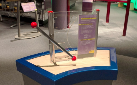 A blue display stand supporting a vertical perspex pane that has a curved cut out within it. Either side of the perspex are two stainless steel poles of which attached to one is a stainless steel bar with red balls attached to each end
