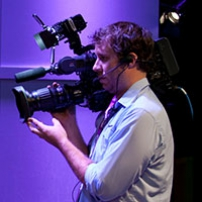 a man in front of a purple wall, holding a professional video camera.