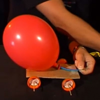A inflated balloon attached to a piece of flat wood that has wheels attached underneath.