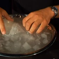 A pair of hands holding a plastic soft drink bottle that is in a bowl filled with water and ice cubes.