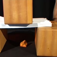 A wooden cube sitting on a corrugated folder paper bridge.