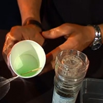 Two hands holding a paper cup with green liquid inside, next to a clear pepper grinder.