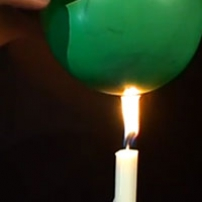 The bottom of a inflated green balloon being touched by the flame of a white candle under it.