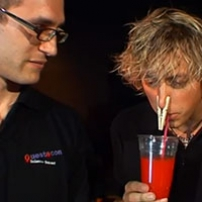 A man wearing glasses looks on at another man with a wooden clothes peg on his nose, sip through a draw of a red drink in a plastic cup.