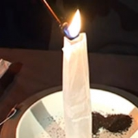 A vertical cylindrical paper tube sitting on a white plate, has a flame at the top.