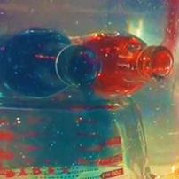 A red and blue drink bottle, both suspended in a tub of water, have red liquid floating up and blue liquid sinking down.