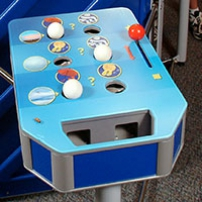 A blue table that has white balls, holes and a red lever in the top.