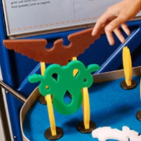 A blue and grey exhibit table and matching information panel with red, green, white and yellow plastic animal shapes on the table top.