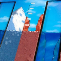 A triangular prism shaped display panel in blue and brown that represents mountains and under the sea.