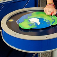 A blue and beige round table has a flat earth picture on top with a red knob, which has a child's hand moving it.
